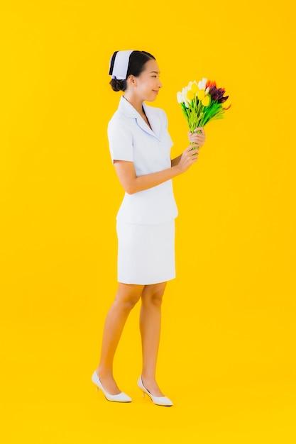 Portrait Belle Jeune Femme Asiatique Thai Infirmière Avec Fleur Photo gratuit