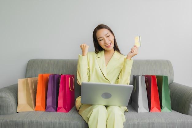 Portrait Belle Jeune Femme Asiatique Utilise Un Ordinateur Portable Avec Carte De Crédit Pour Les Achats En Ligne Sur Le Canapé à L'intérieur Du Salon Photo gratuit