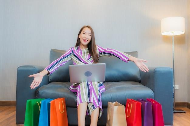 Portrait Belle Jeune Femme Asiatique Utilise Un Ordinateur Portable Ou Un Téléphone Intelligent Mobile Avec Carte De Crédit Pour Les Achats En Ligne Photo gratuit