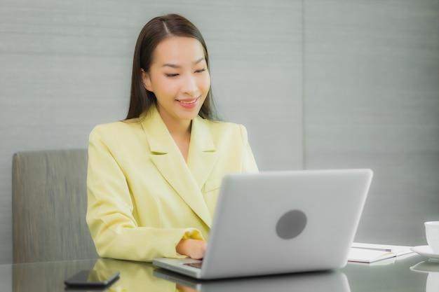 Portrait Belle Jeune Femme Asiatique Utiliser Un Ordinateur Portable Avec Un Téléphone Mobile Intelligent Sur La Table De Travail à L'intérieur De La Salle Photo gratuit