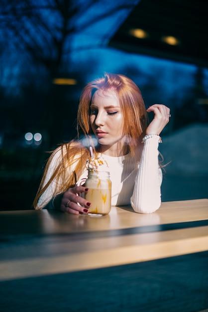 Portrait d'une belle jeune femme assise au café avec un pot de smoothie Photo gratuit