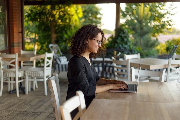 Portrait D'une Belle Jeune Femme Assise à La Table En Tapant Sur L'ordinateur Portable Photo Premium