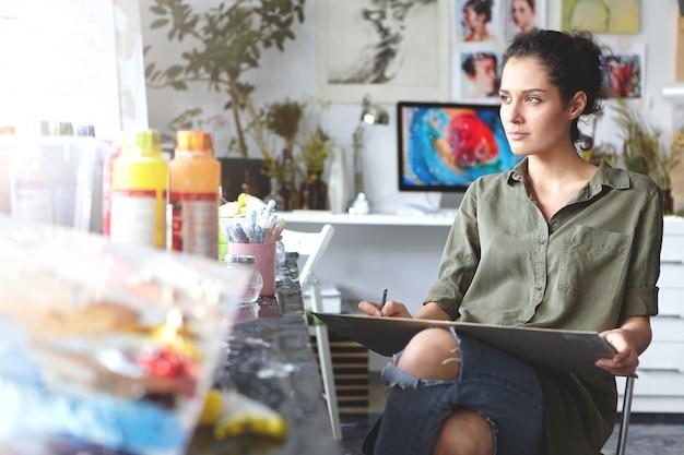 Portrait De La Belle Jeune Femme Brune Réfléchie Artiste Portant Chemise Kaki Et Jeans Déchirés Assis Sur Une Chaise à L'atelier à Domicile Photo gratuit