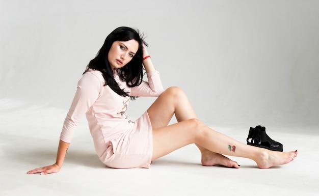 Portrait D'une Belle Jeune Femme Brune Vêtue D'une Robe Rose Assise Sur Le Sol Photo Premium