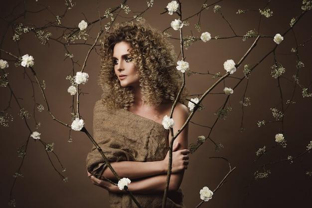 Portrait De Belle Jeune Femme Avec Une Coiffure Afro Et Beau Maquillage Avec Beaucoup De Fleurs Blanches Sur Le Mur Photo Premium