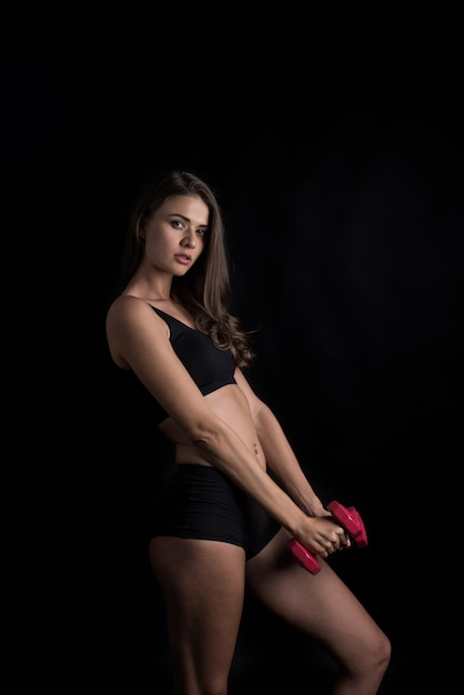 Portrait de la belle jeune femme faisant des exercices physiques avec des haltères Photo gratuit