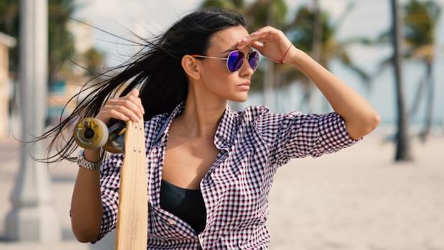 Portrait de la belle jeune femme avec long board sur la plage de hollywood à miami, en floride. image filtrée. Photo Premium