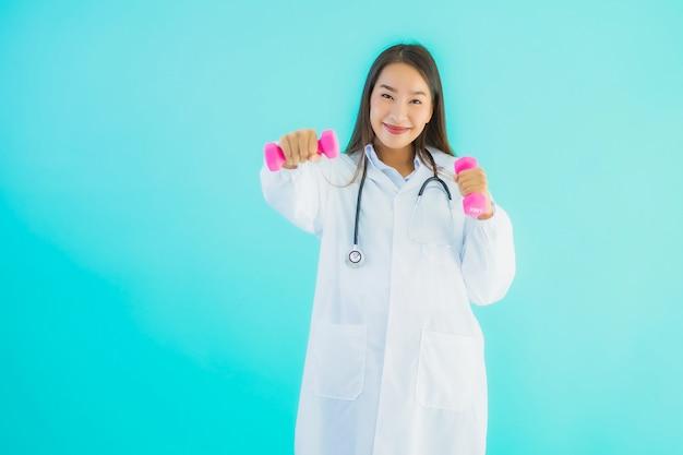 Portrait Belle Jeune Femme Médecin Asiatique Avec Haltère Photo gratuit