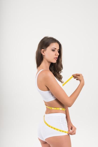 Portrait de la belle jeune femme mesurant sa taille avec un ruban à mesurer Photo gratuit