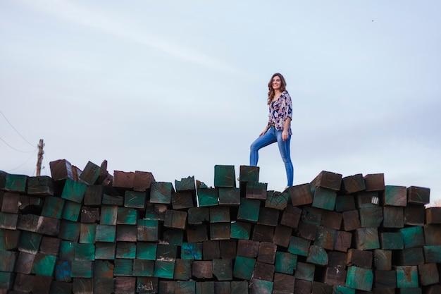 Portrait d'une belle jeune femme portant des vêtements décontractés, debout sur une montagne de blocs de bois verts Photo Premium