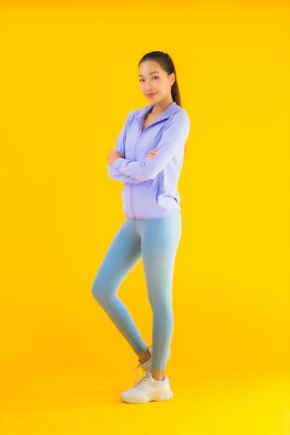 Portrait Belle Jeune Femme Sport Asiatique Prête Pour L'exercice Sur Jaune Photo gratuit