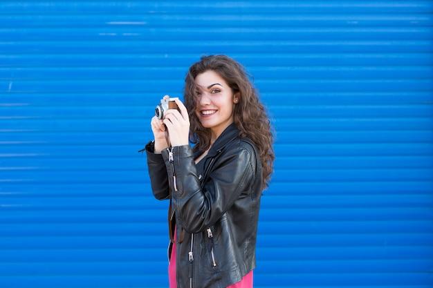 Portrait d'une belle jeune femme tenant un appareil photo vintage sur bleu. Photo Premium