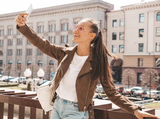 Portrait De La Belle Jeune Fille Brune Souriante En Veste Hipster D'été. Modèle Prenant Selfie Sur Smartphone. Photo gratuit