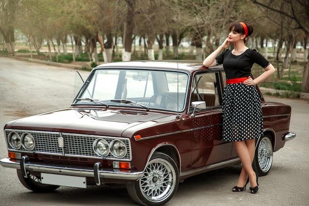 Portrait D'une Belle Jeune Fille Caucasienne Dans Une Robe Vintage Noire, Posant Près D'une Voiture Vintage Photo Premium