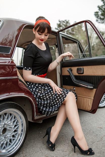 Portrait d'une belle jeune fille caucasienne dans une robe vintage noire Photo Premium