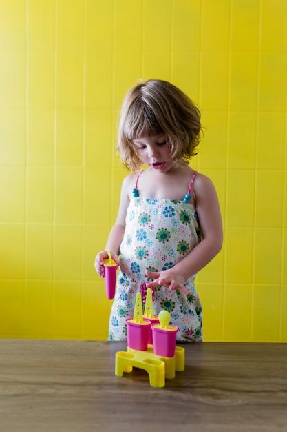Portrait D'une Belle Jeune Fille Enfant Jouant Avec Des Glaces à La Maison. Bonheur Et Style De Vie à L'intérieur. été. Mur Jaune Photo Premium