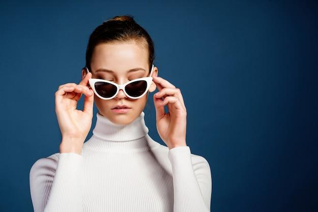 Portrait D'une Belle Jeune Fille à Lunettes De Soleil Sur Fond Bleu Photo Premium
