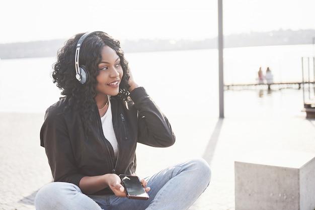 Portrait D'une Belle Jeune Jolie Fille Afro-américaine Assise Sur La Plage Ou Le Lac Et écouter De La Musique Dans Ses écouteurs Photo Premium