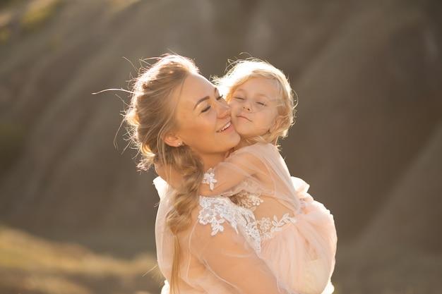 Portrait D'une Belle Jeune Maman Tient Sa Fille Bien-aimée Dans Ses Bras. Amour Parental, Petite Princesse Photo Premium
