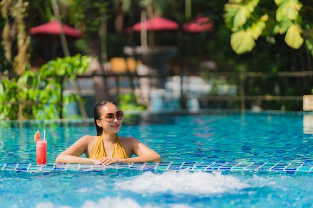 Portrait belle loisirs de jeune femme asiatique se détendre sourire avec du jus de pastèque autour de la piscine dans l'hôtel resort Photo gratuit