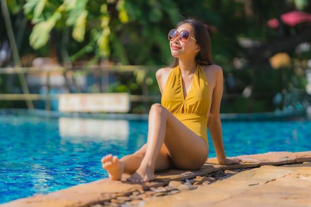 Portrait belle loisirs de jeune femme asiatique se détendre sourire et heureux autour de la piscine dans l'hôtel resort Photo gratuit