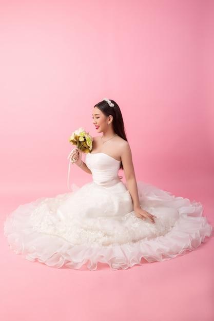 Portrait de la belle mariée asiatique en studio rose Photo gratuit