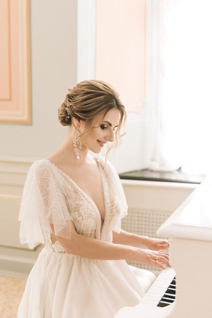 Portrait D'une Belle Mariée à Côté D'un Piano Dans Un Intérieur Luxueux Photo Premium