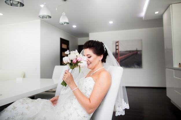 Portrait de la belle mariée heureuse assis sur un canapé Photo Premium