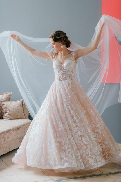 Portrait de la belle mariée en robe vintage blanche avec une fleur dans ses mains, posant sous le voile sur fond gris Photo Premium