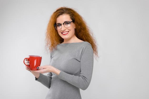 Portrait De Belle Rousse Heureuse Jeune Femme Réussie Dans Des Vêtements Gris Dans Des Verres à Boire Du Café Sur Fond Gris Photo Premium