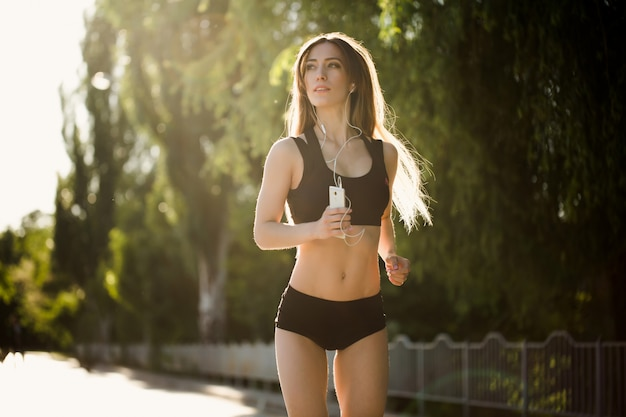 Portrait D'une Belle Et Sportive Jeune Femme écoutant De La Musique Ayant Une Pause Après Avoir Couru à L'extérieur Photo Premium