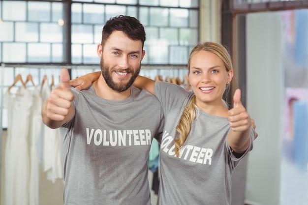 Portrait de bénévoles souriants donnant les pouces au bureau Photo Premium
