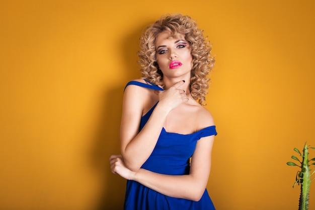 Portrait d'une blonde de luxe dans un studio sur jaune Photo Premium