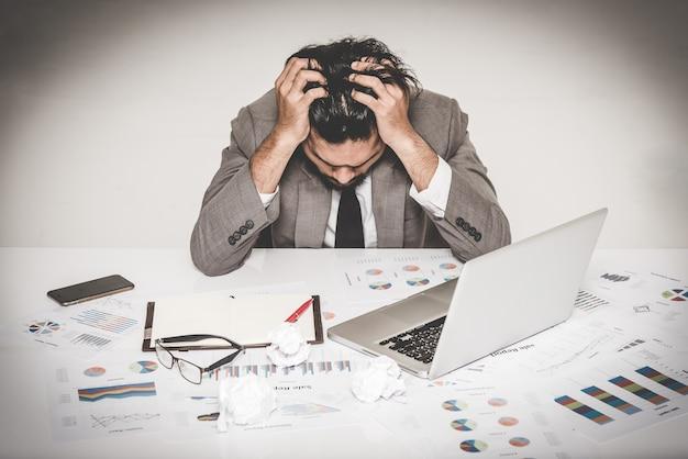 Portrait de burnout homme d'affaires stressé tenant sa tête avec les deux mains au travail Photo Premium
