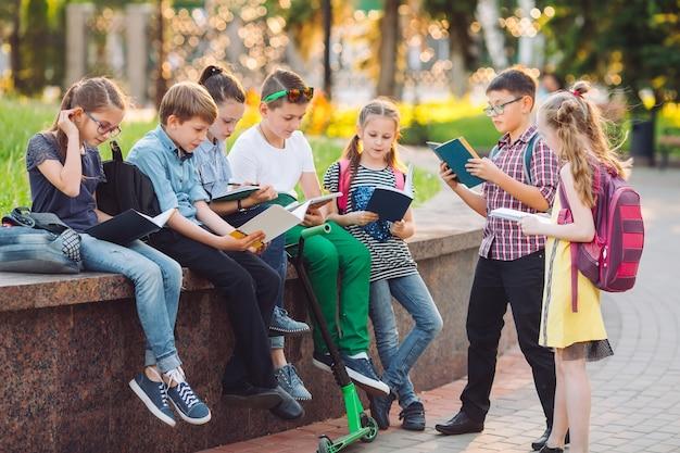 Portrait De Camarades De Classe Heureux. Camarades Assis Avec Des Livres Sur Un Banc En Bois Dans Un Parc De La Ville Et étudie Par Une Journée Ensoleillée. Photo Premium