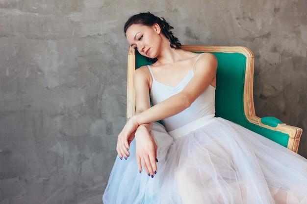 Portrait candide de la ballerine de la danseuse en robe bleue claire jupe tutu posant assis sur une chaise de vinage en studio loft Photo Premium