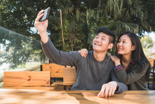 Portrait D'un Charmant Couple Asiatique S'amuser Et Prendre Un Selfie Avec Un Téléphone Portable Dans Un Café. Photo gratuit