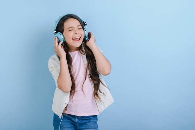 Portrait d'une charmante petite fille aux yeux fermés dans des écouteurs, écoutant de la musique et chanter Photo Premium