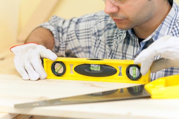 Portrait d'un charpentier effectuant un travail de précision dans une maison Photo Premium
