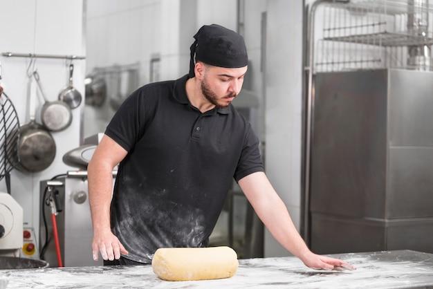 Portrait d'un chef pâtissier dans la cuisine prêt à pétrir la pâte. Photo Premium