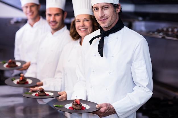 Portrait de chefs heureux présentant leurs assiettes à dessert Photo Premium