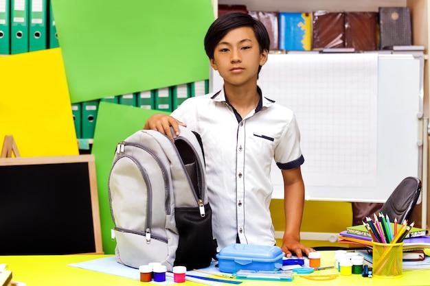 Portrait Classman écolier étude Assis Livres Asiatique Garçon Leçon Conseil Scolaire Cartable Sac à Dos Crayon Globe Jaune Vert Photo Premium