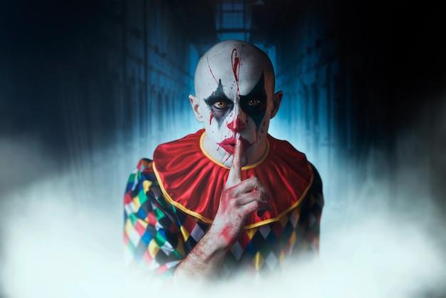 Portrait De Clown Sanglant Fou Montre Le Signe Calme, Le Visage Dans Le Sang. Homme Avec Du Maquillage En Costume D'halloween, Fou Maniaque Photo Premium