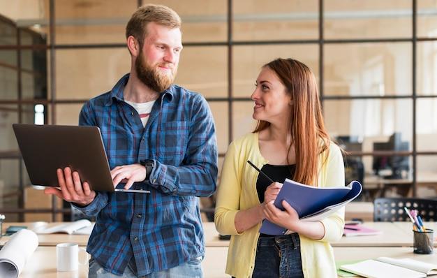 Portrait de collègues se regardant et souriant au bureau Photo gratuit