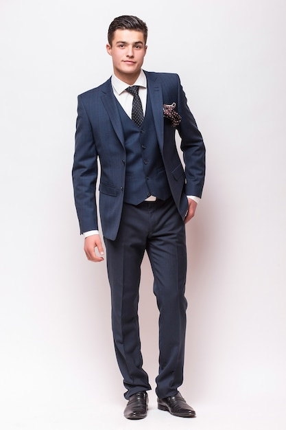 Portrait Complet Du Corps D'un Homme D'affaires En Costume Debout Sur Un Mur Blanc Isolé Photo gratuit
