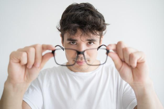 Portrait, de, concentré, jeune étudiant, regarder lunettes Photo gratuit