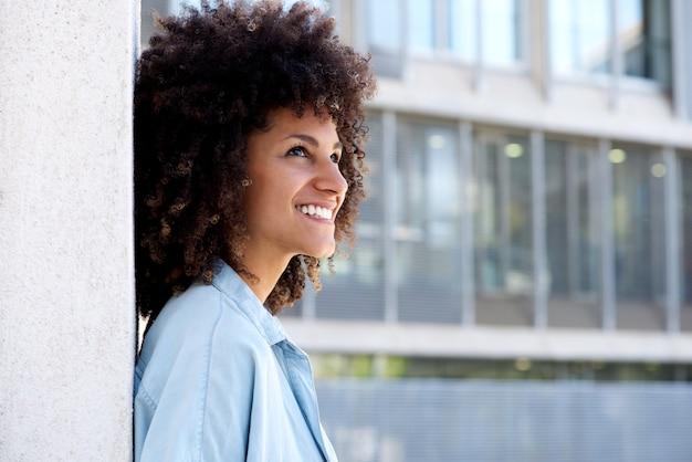 Portrait côté, de, femme souriante, debout, dehors, par, bâtiment urbain Photo Premium