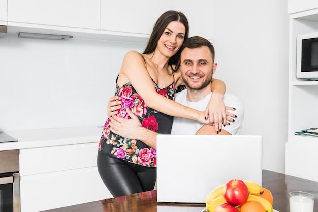 Portrait d'un couple d'amoureux souriant embrassant en regardant la caméra Photo gratuit