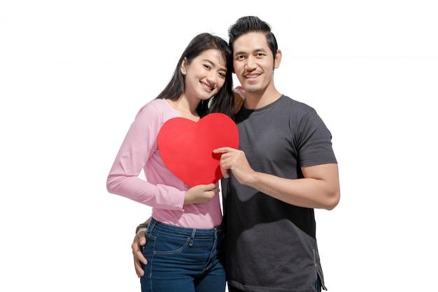 Portrait de couple asiatique embrasse et tenant des coeurs de papier rouge Photo Premium