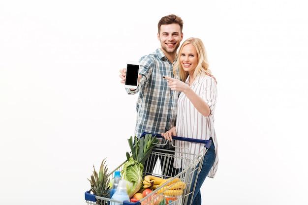 Portrait D'un Couple Heureux Montrant Un Téléphone Mobile à écran Blanc Photo gratuit